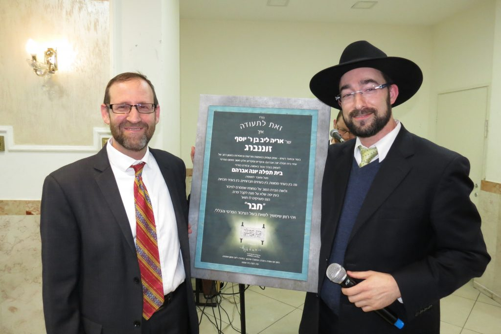 "Dovid Kallus presenting Aryeh Sonnenberg with a ""Chaver"" award at the BTYA Melaveh Malkah"